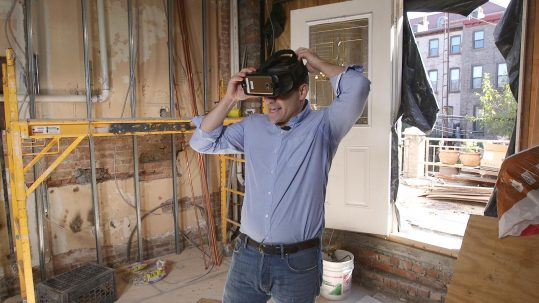 Photo of guy putting on VR goggles in gutted room